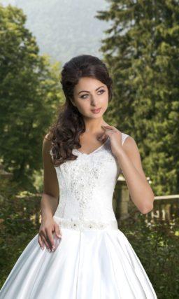 Свадебное платье с объемной юбкой и изящным облегающим корсетом, украшенным кружевом.