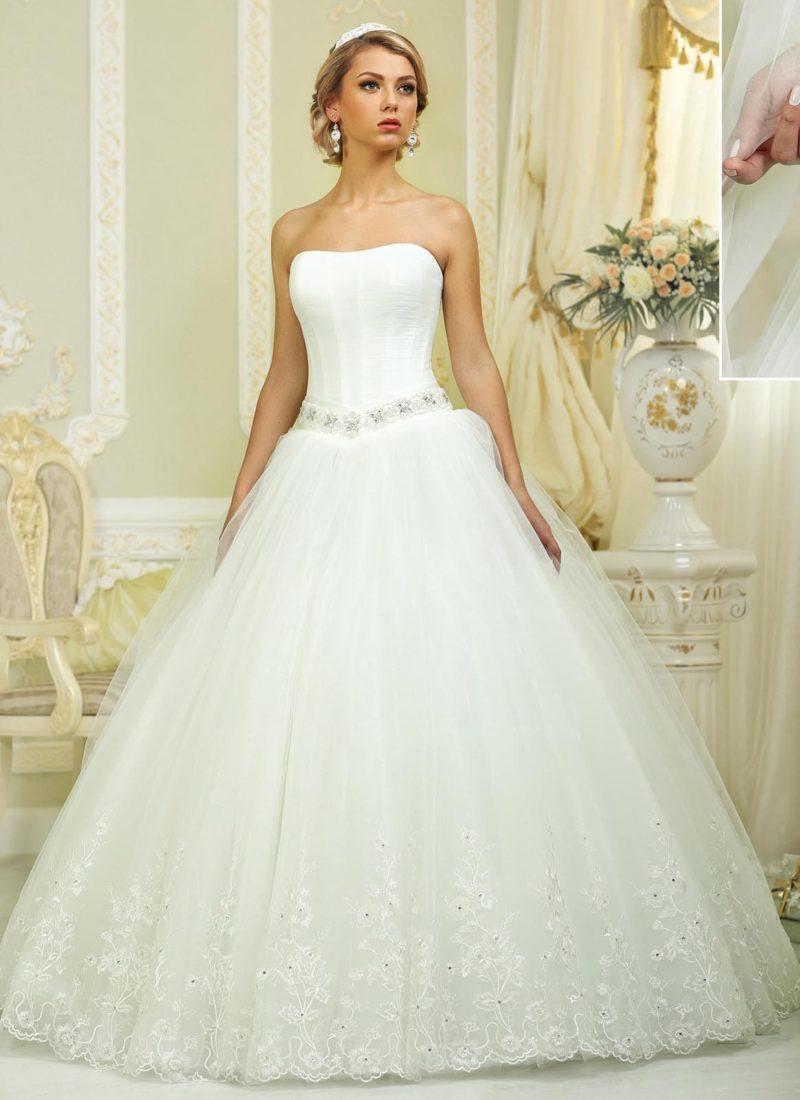 Лаконичное свадебное платье с пышной юбкой из нескольких слоев ткани и узким сияющим поясом.