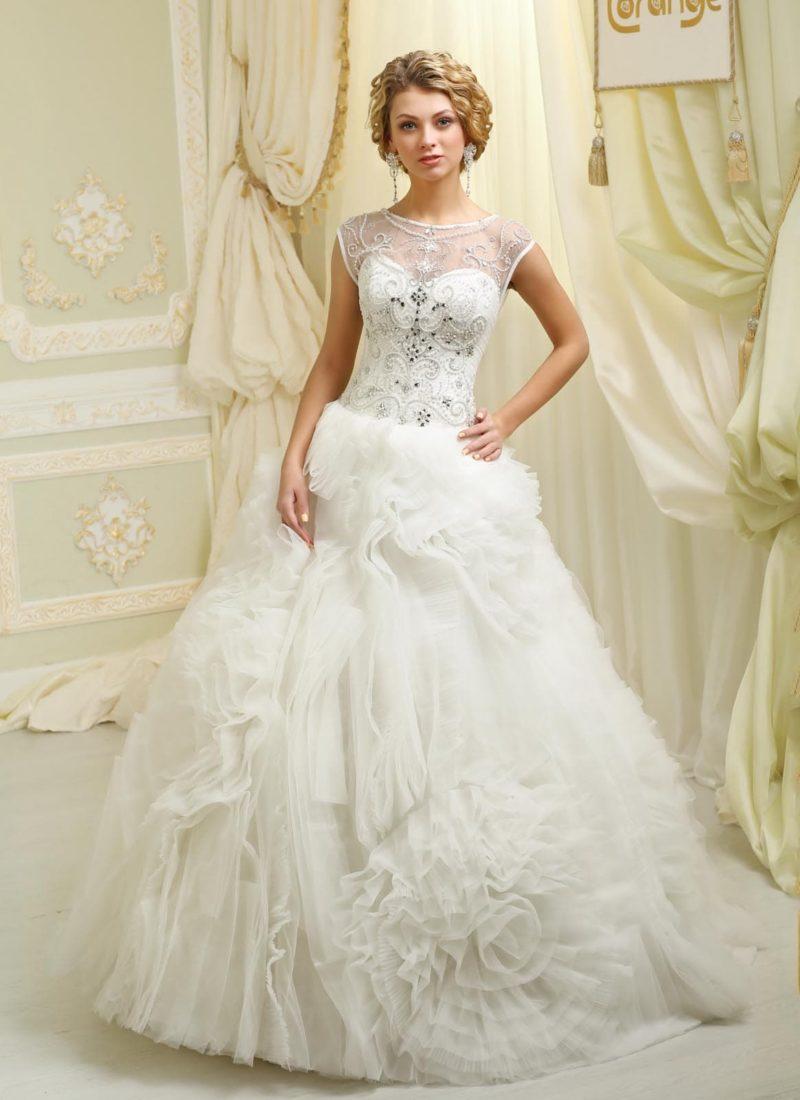 Шикарное свадебное платье с оборками по подолу и закрытым лифом из тонкой ткани.
