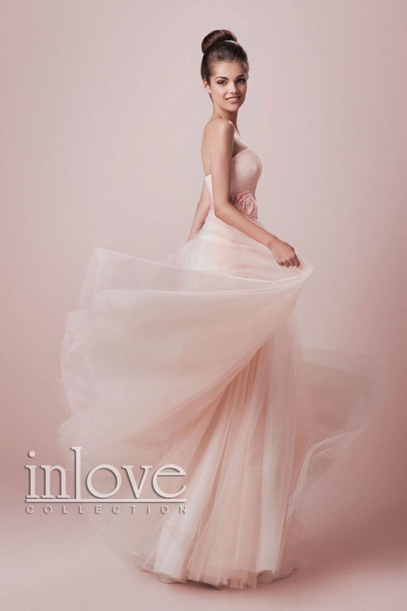 Нежное свадебное платье персикового оттенка с открытым лифом в форме сердца и многослойной юбкой.