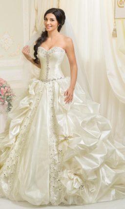 Пышное свадебное платье с глянцевыми оборками по юбке и открытым корсетом с вышивкой.