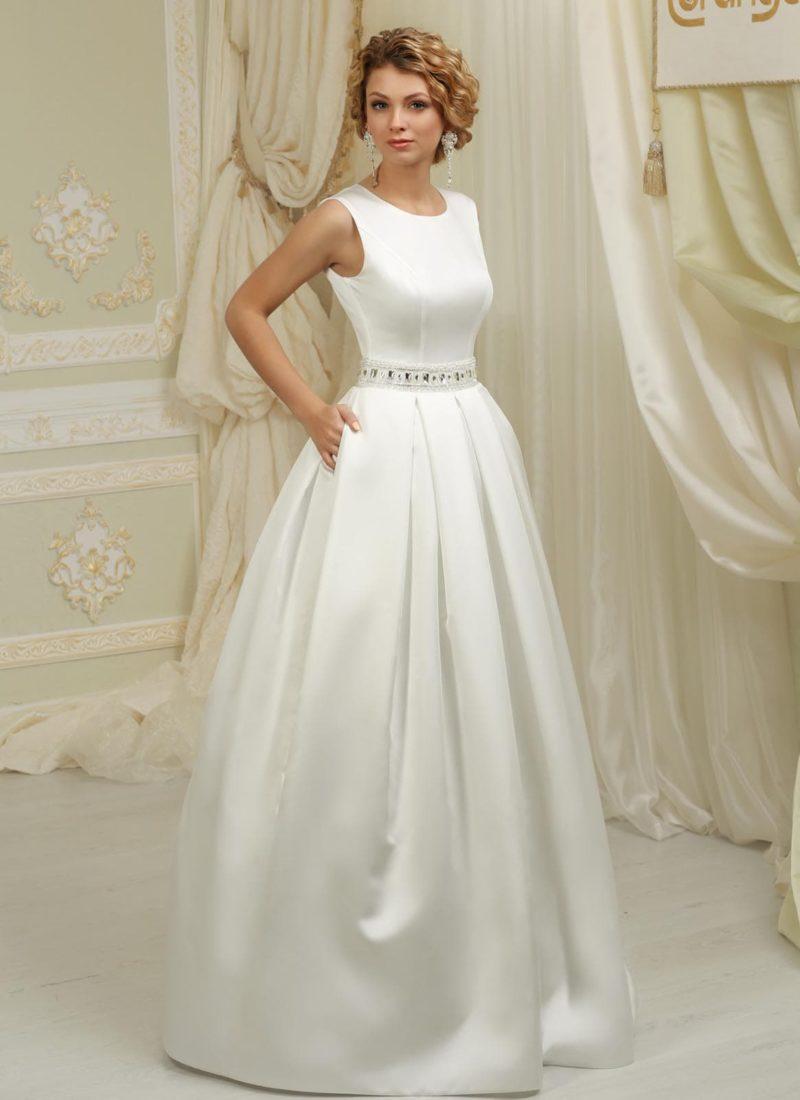 Атласное свадебное платье с пышной юбкой, округлым вырезом под горло и широким поясом.