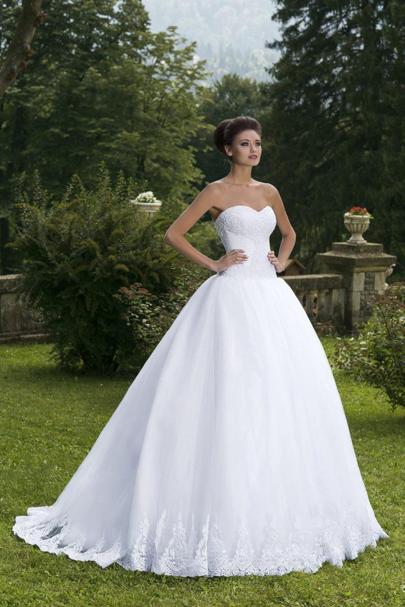 Классическое свадебное платье пышного силуэта, с открытым декольте и торжественным шлейфом.