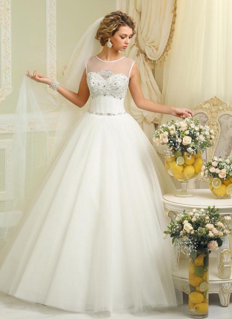 Закрытое свадебное платье пышного кроя с полупрозрачной вставкой над расшитым бисером лифом.