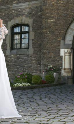 Изысканное свадебное платье, дополненное полупрозрачным кружевным болеро с длинным рукавом.