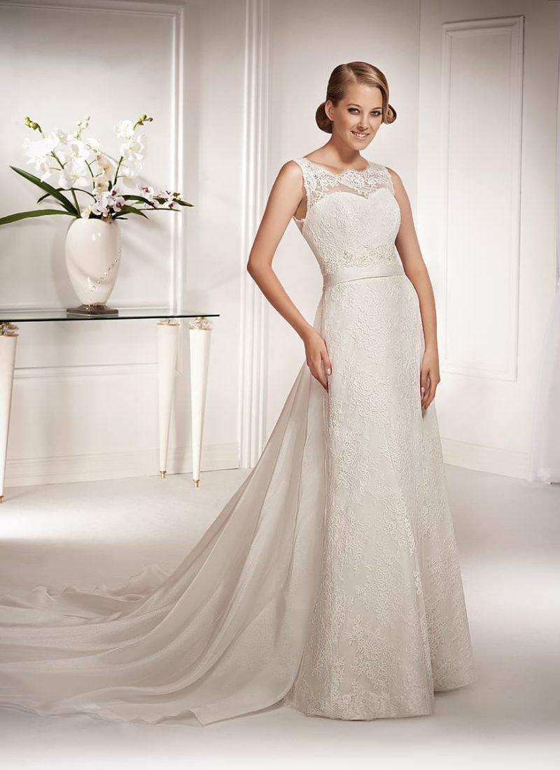 Прямое свадебное платье с фигурным округлым вырезом и лаконичным поясом на талии.