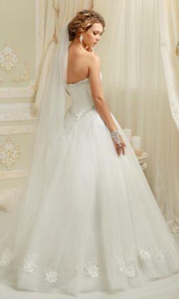 Торжественное свадебное платье с открытым лифом и объемной отделкой многослойного подола.
