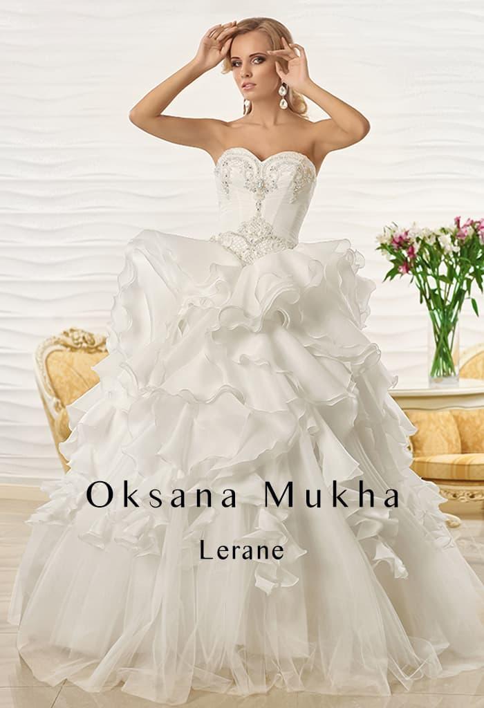 Открытое свадебное платье с оборками по верху подола пышной юбки и вышивкой по корсету.