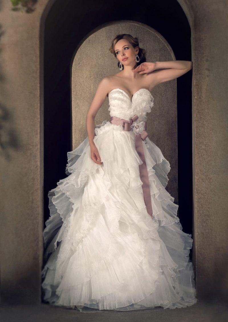 Пышное свадебное платье с полупрозрачными оборками и широким розовым поясом из атласа.