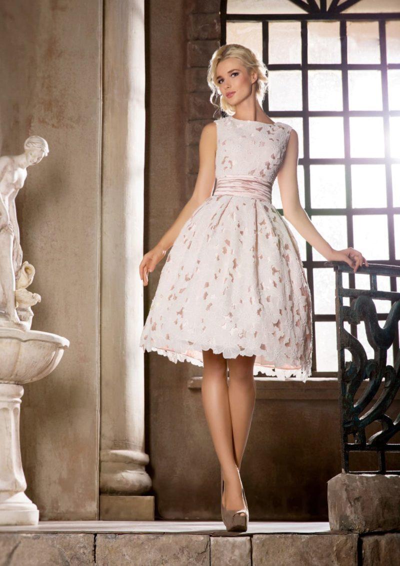 Кокетливое свадебное платье длиной до колена, с розовой подкладкой и кружевным декором.