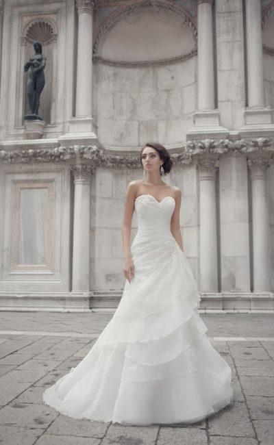 Свадебное платье с юбкой кроя «трапеция», украшенной драпировками, и открытым корсетом.