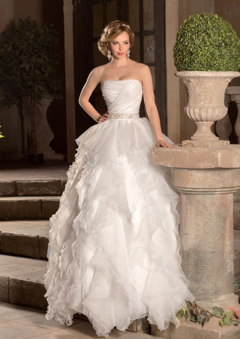 Открытое свадебное платье с юбкой, покрытой полупрозрачными оборками, и лифом прямого кроя.