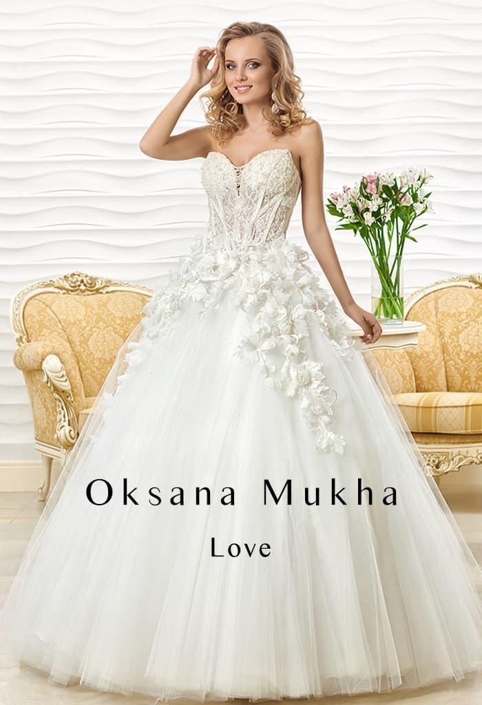 Драматичное свадебное платье пышного кроя с объемным декором верха подола и фактурным лифом.