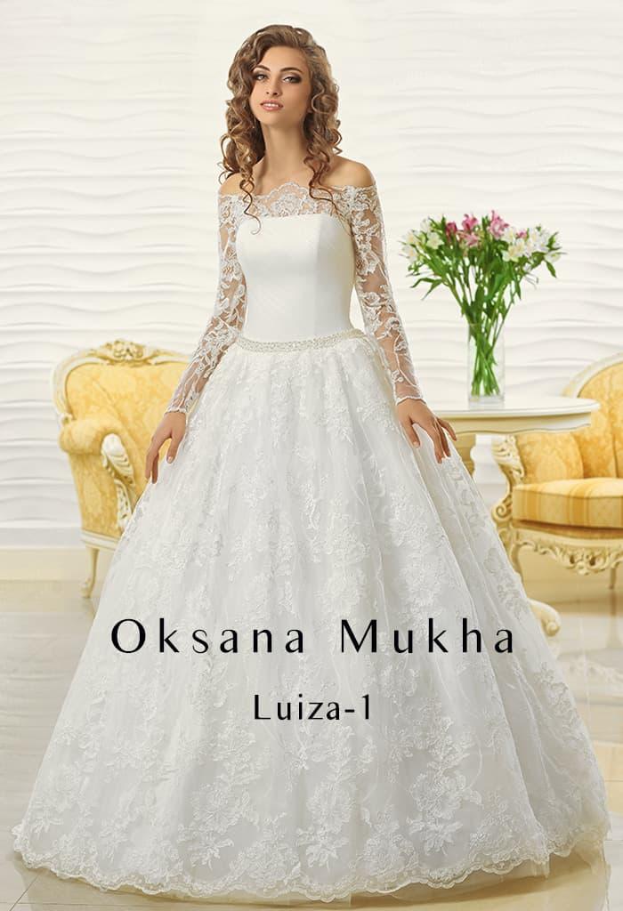 Притягательное пышное свадебное платье с портретным декольте и кружевным рукавом.
