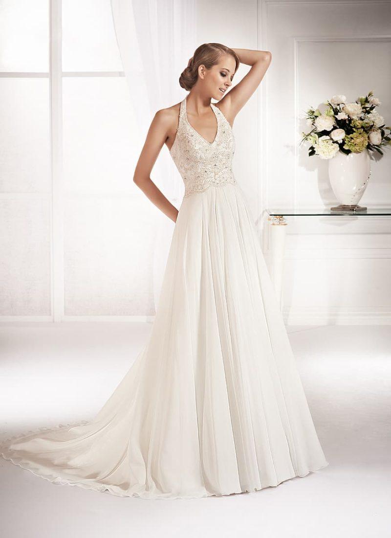 Стильное свадебное платье с вертикальными складками по юбке и бретелью халтер.