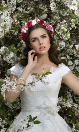 Пышное свадебное платье с аппликациями на юбке и изящным облегающим верхом.