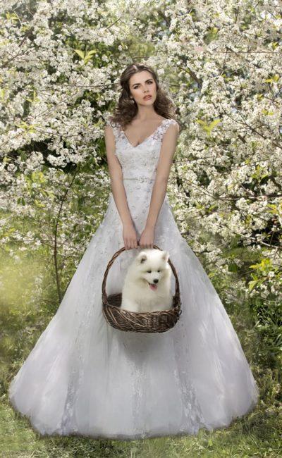 Свадебное платье с V-образными вырезами на лифе и спинке, а также объемным декором.