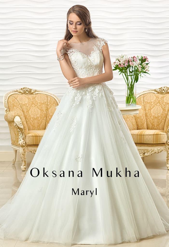 Пышное свадебное платье с тонкой вставкой над декольте и кружевным декором.