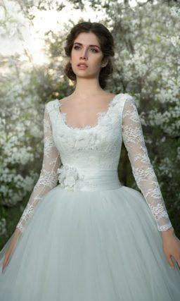 Пышное свадебное платье с округлым вырезом и широким поясом из глянцевого атласа.