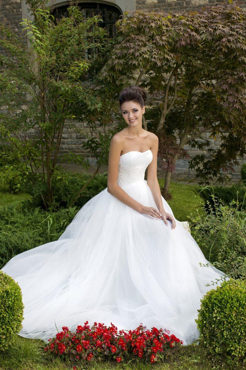 Романтичное свадебное платье с пышной юбкой и кружевным декором по линии талии.