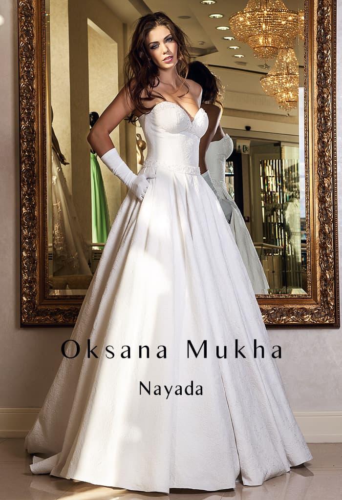 Пышное свадебное платье с подчеркнутым декольте и элегантным поясом.