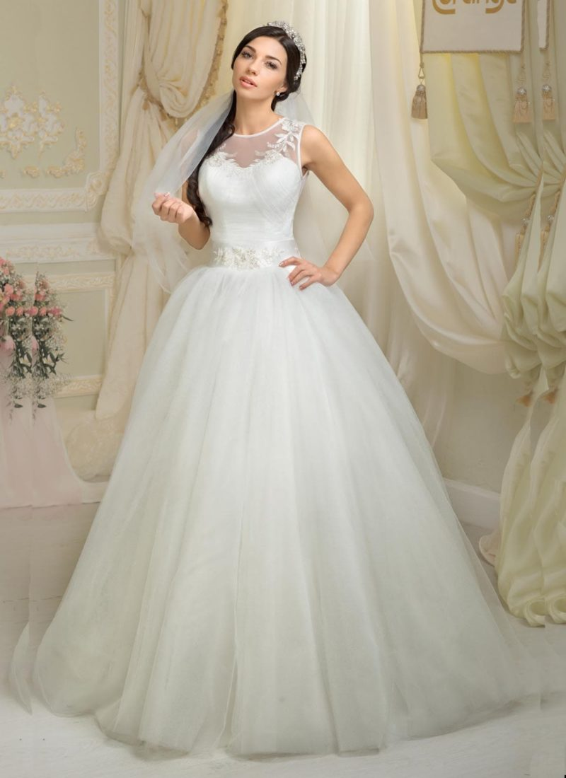 Свадебное платье с многослойной юбкой с прозрачным верхом и широким поясом из атласа.