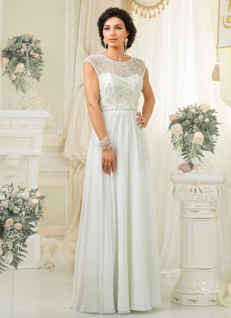 Стильное свадебное платье прямого кроя с закрытым верхом из тонкой ткани, покрытой бисером.