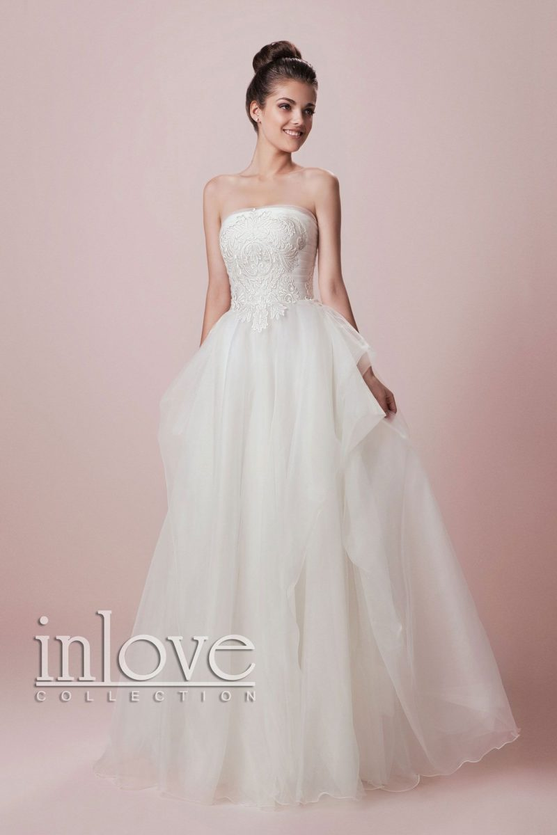 Утонченное свадебное платье с многослойным объемным подолом и лаконичным прямым вырезом.