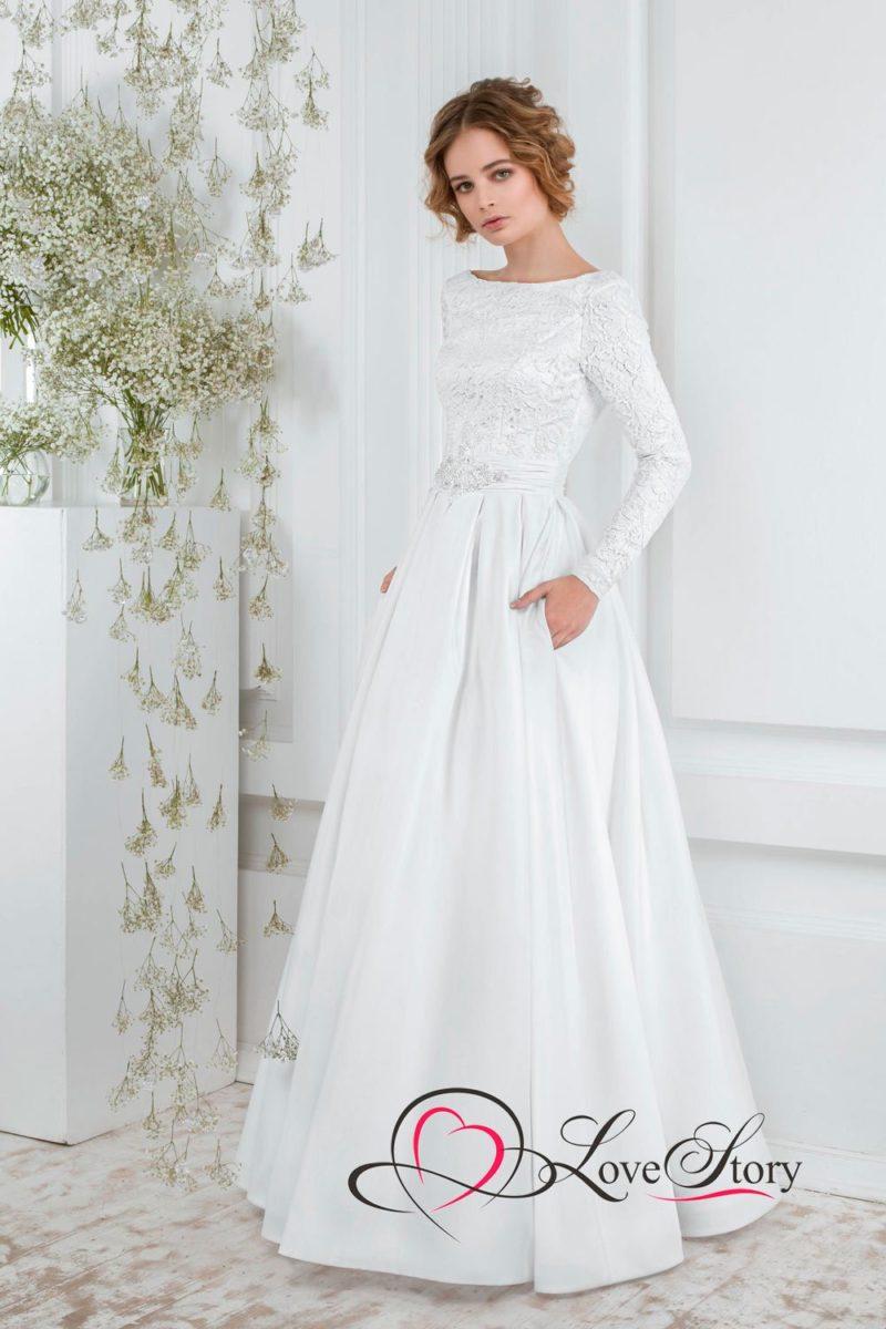Атласное свадебное платье со скрытым карманом и длинным рукавом, покрытым кружевом.