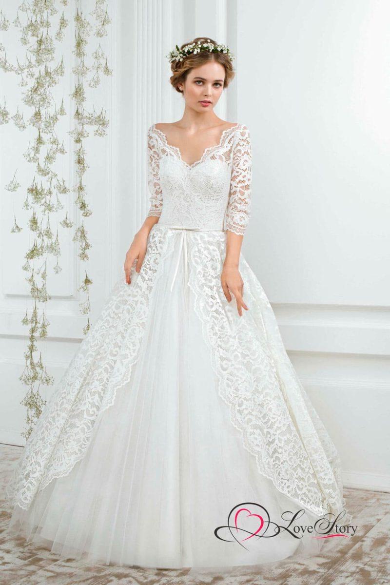 Пышное свадебное платье, дополненное по верху кружевом, создающим V-образный вырез.