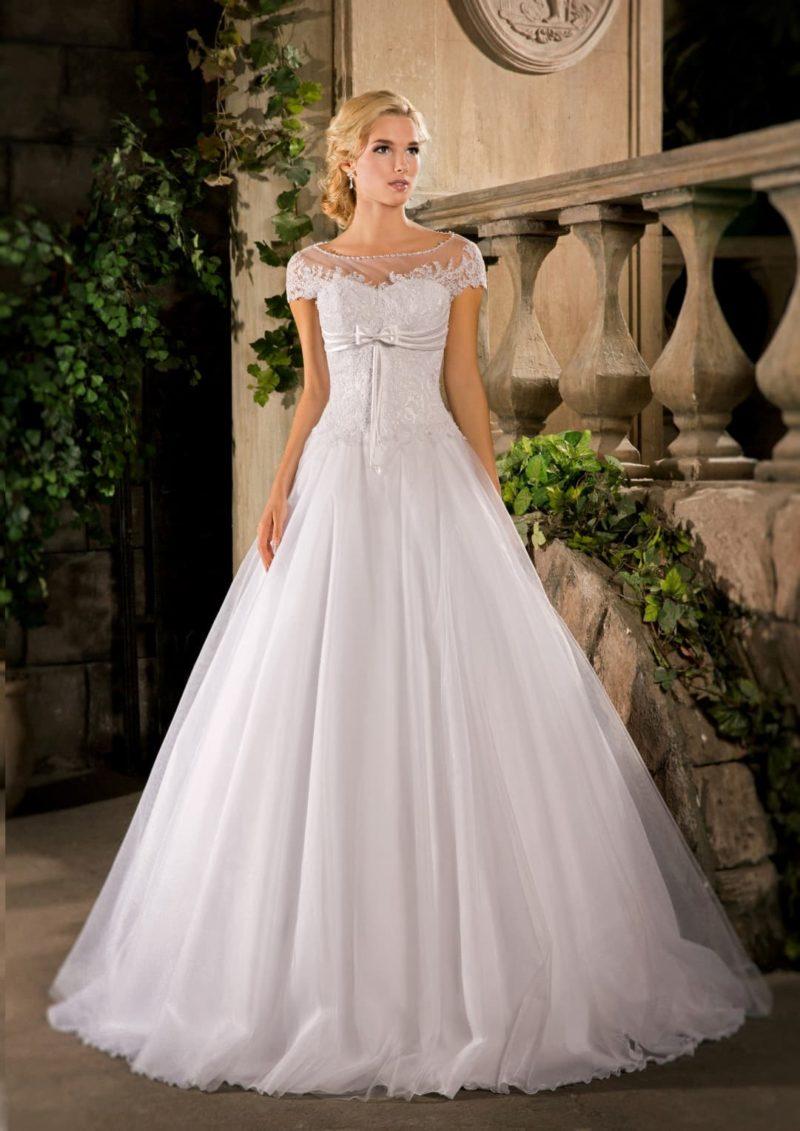 Деликатное свадебное платье воздушного кроя с округлым декольте и кружевными аппликациями.