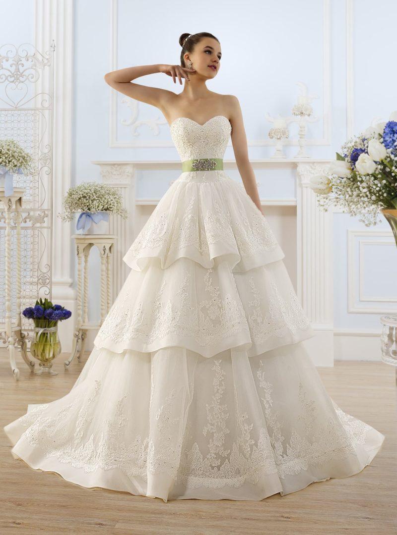 Торжественное свадебное платье с многоярусной кружевной юбкой и зеленым поясом.