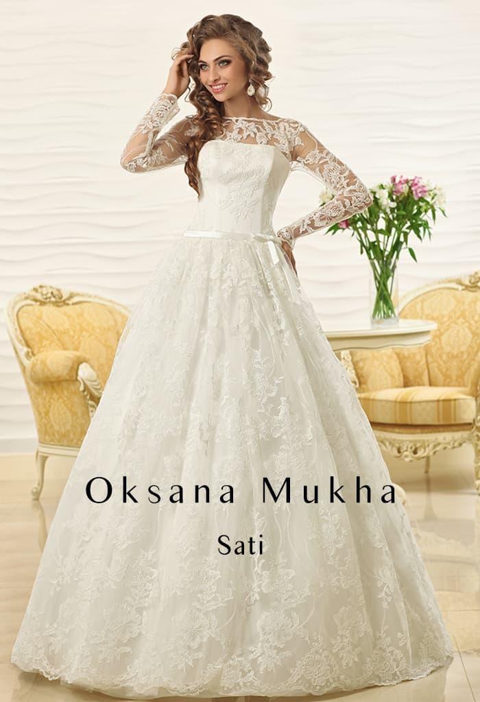 Торжественное свадебное платье пышного кроя с открытой спиной и длинным рукавом.