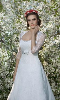 Свадебное платье А-силуэта с завышенной линией талии, выделенной узким поясом с бантом.
