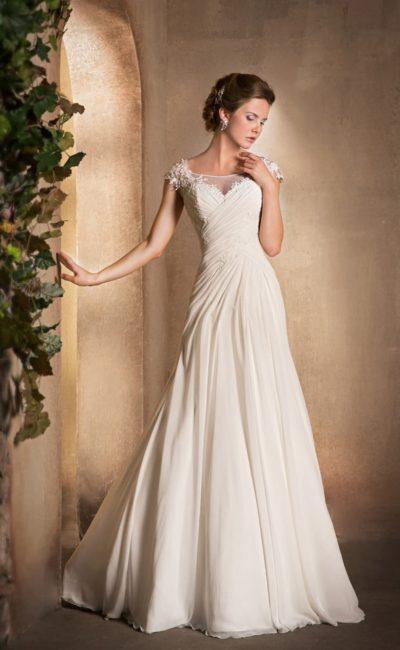 Деликатное свадебное платье с прозрачной вставкой над лифом и нежными драпировками по корсету.