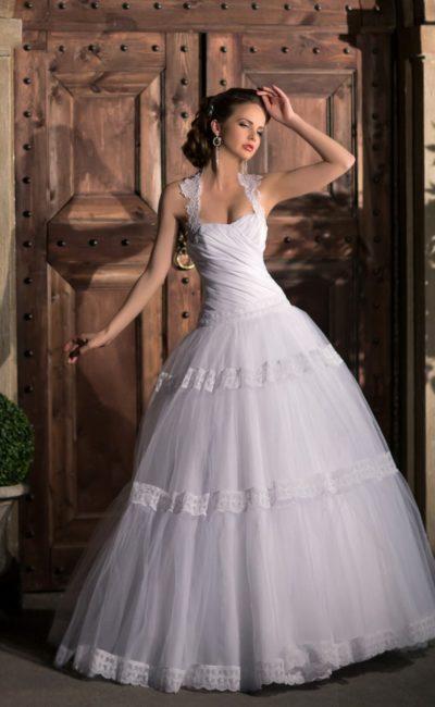 Пышное свадебное платье с горизонтальными полосами декора по подолу и фигурными бретелями.