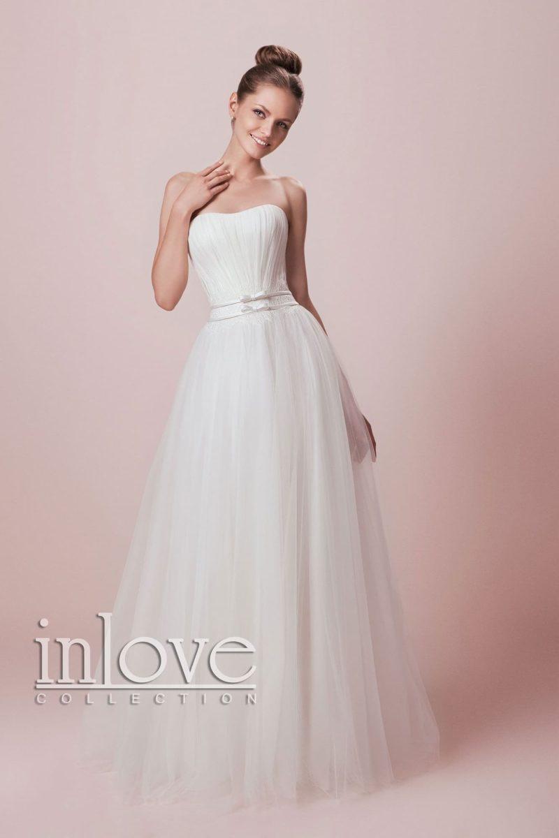 Открытое свадебное платье пышного кроя с деликатным вырезом и изящным поясом на талии.