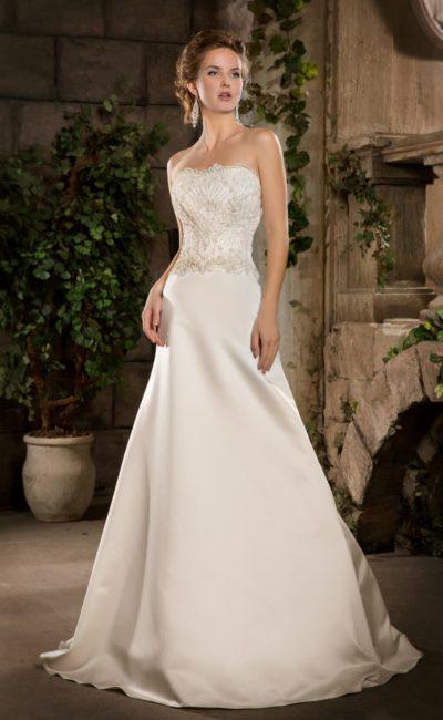 Свадебное платье с лаконичной юбкой «трапеция» и открытым корсетом, покрытым золотистым кружевом.