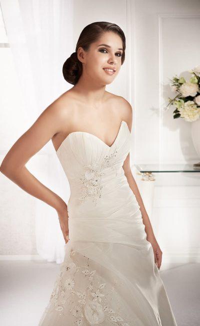 Пышное свадебное платье с глубоким вырезом-сердечком и романтичной отделкой.