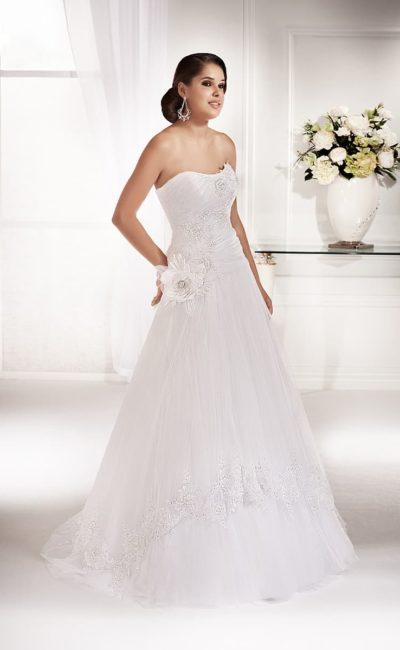 Свадебное платье «трапеция» с деликатным вырезом лифа и крупным бутоном на талии.