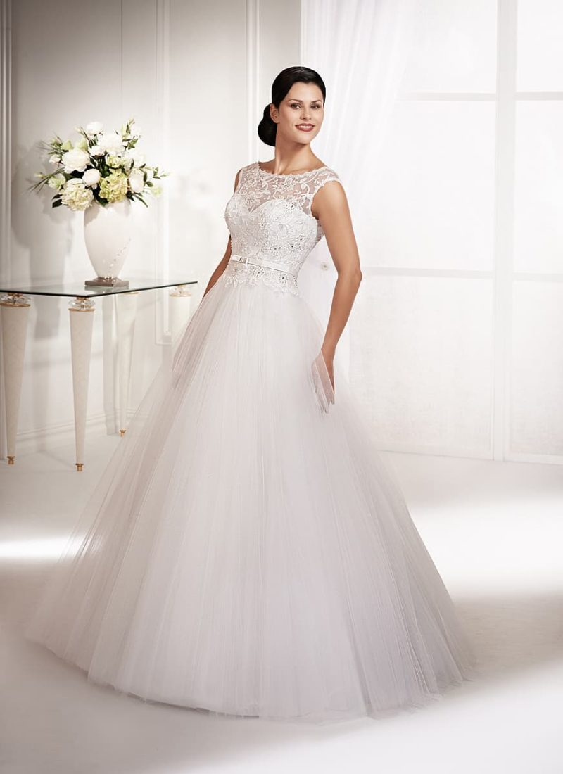 Закрытое свадебное платье с многослойным подолом и кружевным декором корсета.