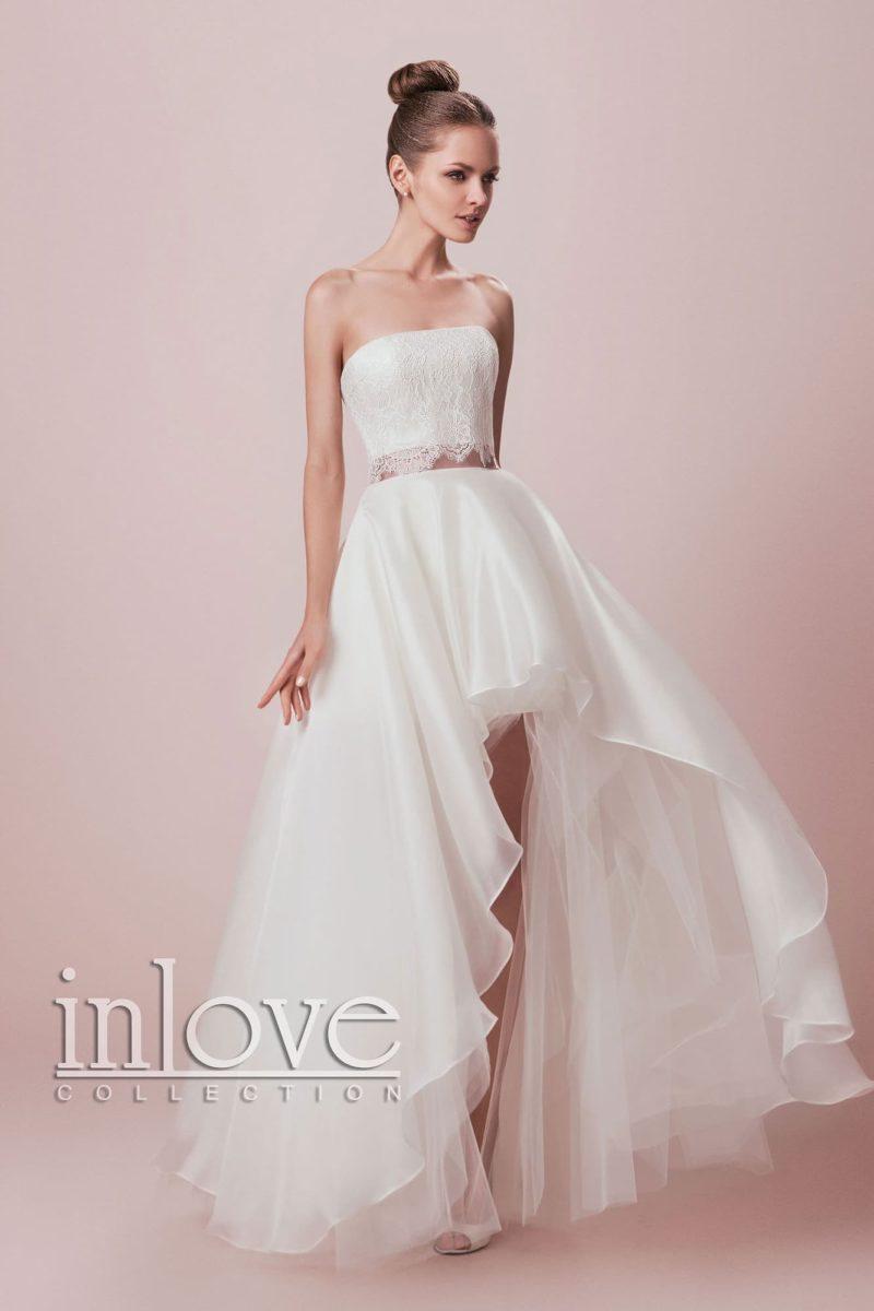 Необычное свадебное платье пышного кроя с укороченным спереди подолом и лифом прямого кроя.