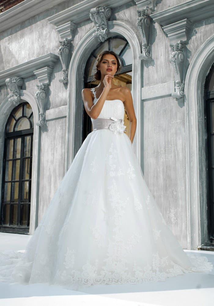 Элегантное свадебное платье с асимметричным лифом и широким лиловым поясом с бутонами сбоку.