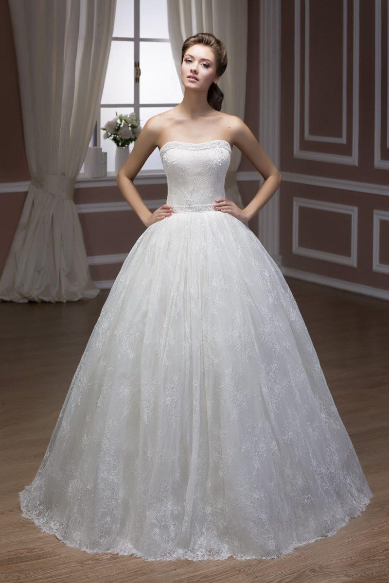 Свадебное платье с открытым декольте и пышной юбкой с кружевной отделкой по всей длине.