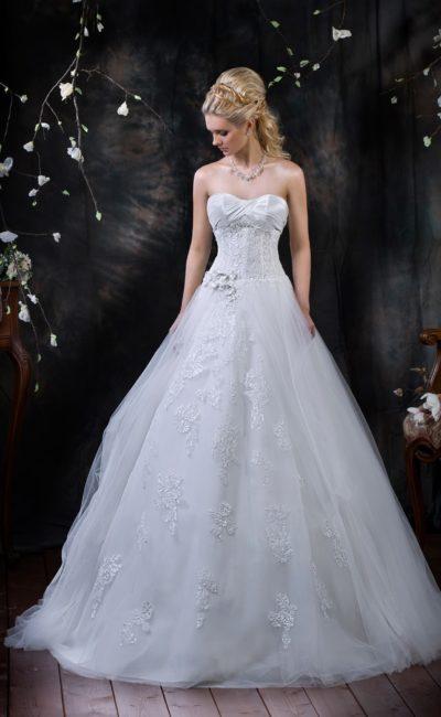 Свадебное платье А-кроя с кружевной отделкой юбки и тюльмарином по бокам подола.