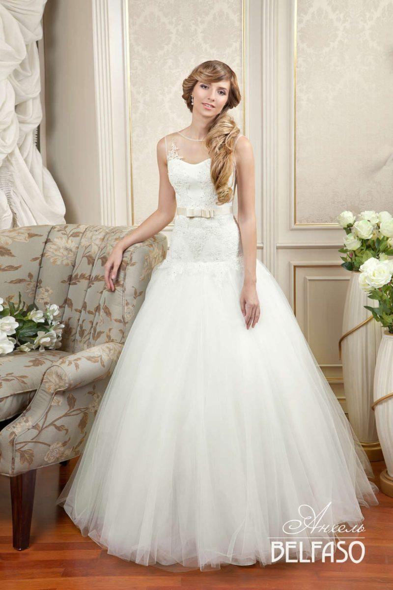 Пышное свадебное платье с облегающим кружевным верхом и заниженной талией.