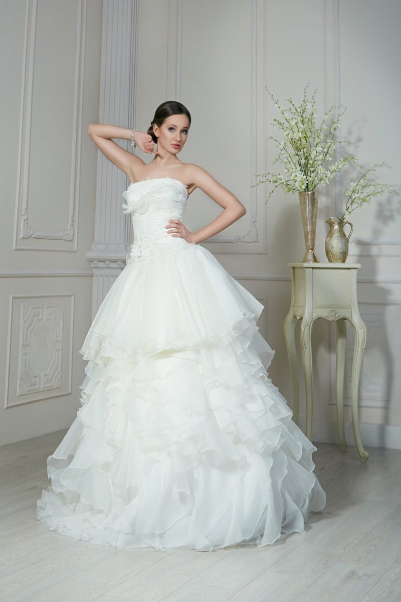 Романтичное свадебное платье с оборками по всей длине пышной юбки и открытым лифом.