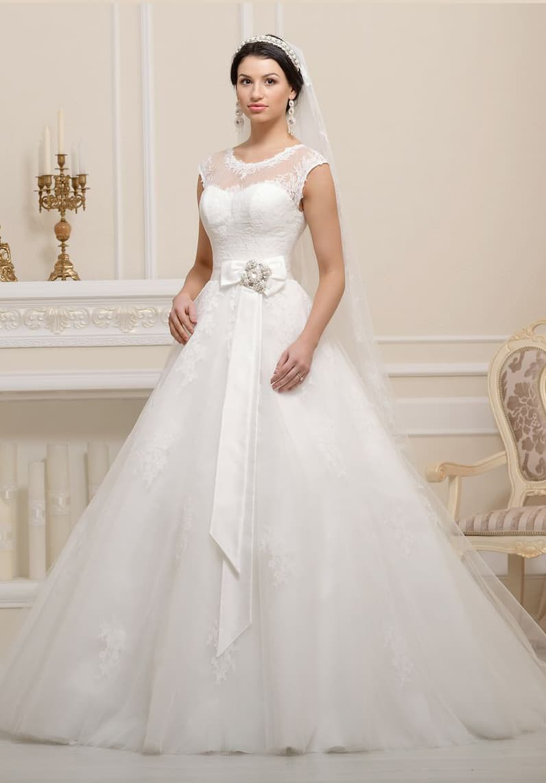 Закрытое свадебное платье с полупрозрачной вставкой над лифом и бантом на уровне талии.