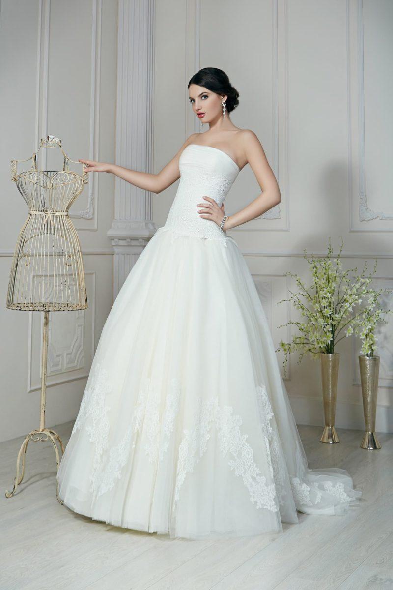 Свадебное платье с открытым корсетом прямого кроя и воздушной юбкой с кружевным декором.