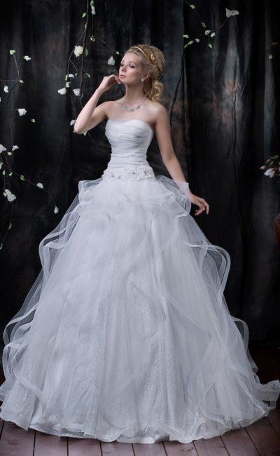 Свадебное платье пышного кроя с фактурной кружевной подкладкой и полупрозрачным верхом юбки.